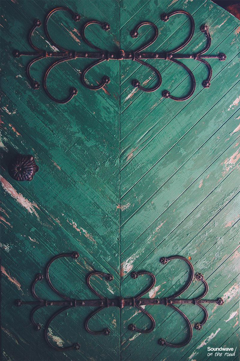 Porte verte sertie de ferraille