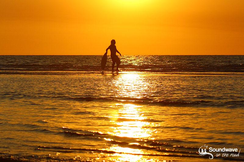 Skimboarder face au coucher de soleil