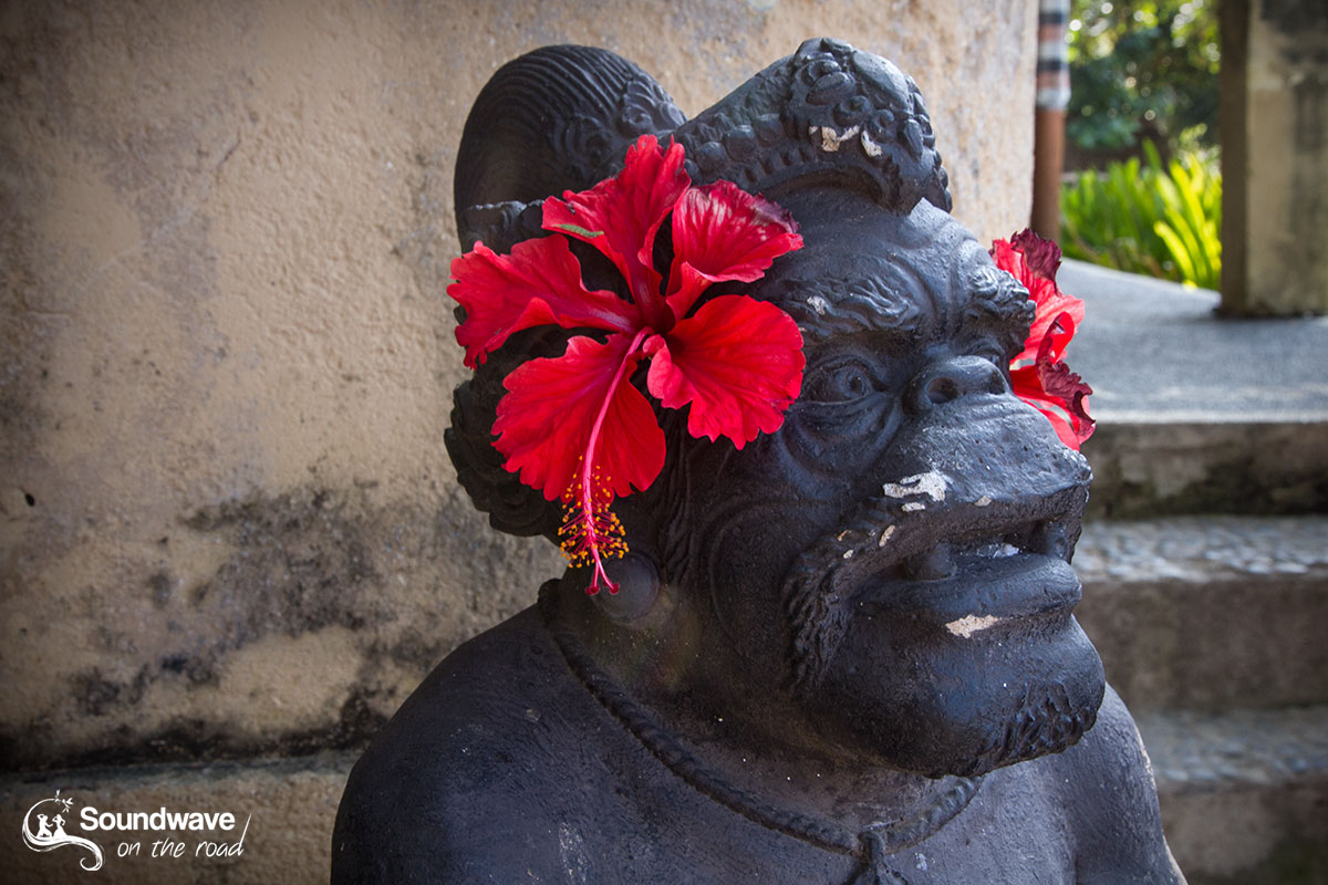Hibiscus red flower on a statue in Nusa Lembongan