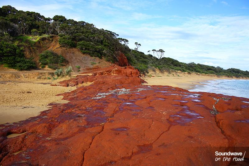 Une langue de rochers rouges vient rencontrer la mer