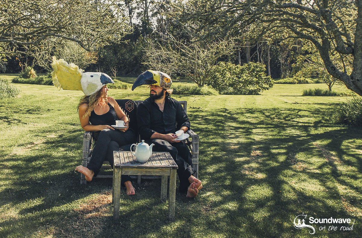 A couple with bird hats in a sunny garden